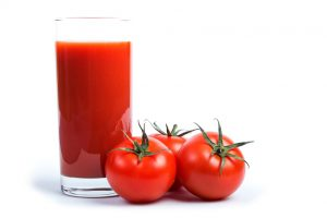 Tasty tomato juice and tomatoes over white.